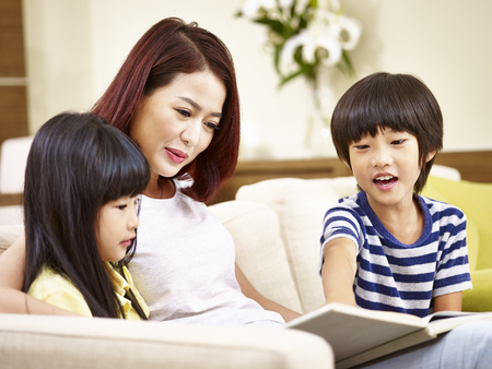 young asian mother and her son and daughter sitting on couch reading a book together.