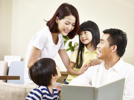 Aziatische ouders moeder en vader en twee kinderen zoon en dochter lezen van een boek vertellen samen een verhaal. Stockfoto
