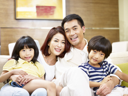 portrait of a happy asian family sitting on couch at home looking at camera smiling.