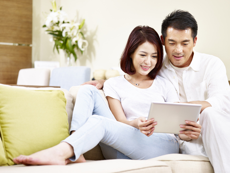 asian couple sitting on family couch in living room using digital tablet together. Banque d'images