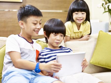 3 아시아 어린이 두 어린 소년 및 집에서 소파에 앉아 한 어린 소녀 비디오 게임 디지털 태블릿, 뒤쪽에 어린 소녀에 초점을 재생합니다.
