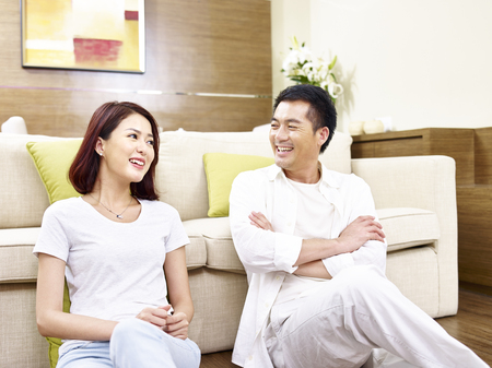 asian couple sitting relaxing chatting on the floor at home. 스톡 콘텐츠