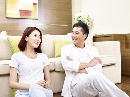 Aziatische paar vergadering ontspannen chatten op de vloer thuis.