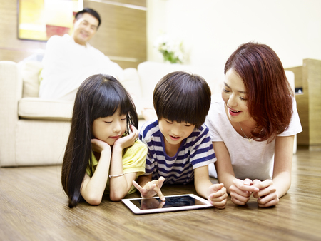 asian mother and two children lying on front on floor playing with digital tablet while father watching in the background.