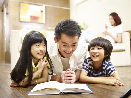 asian father and two children lying on front on floor reading book while mother relaxing in the background. Фото со стока