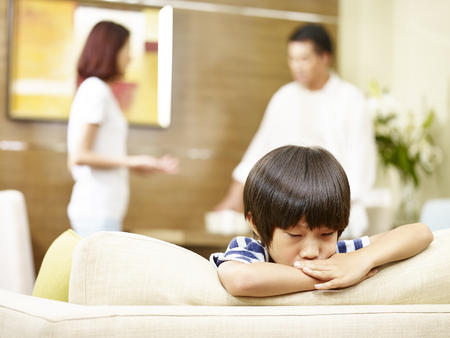 asian child appears sad and unhappy while parents quarreling in the background. Stockfoto