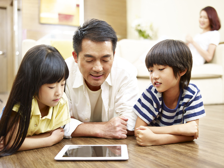 asian mother and two children lying on front on floor playing with digital tablet while mother watching in the background.