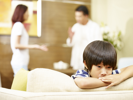 asian child appears sad and unhappy while parents quarreling in the background. 版權商用圖片