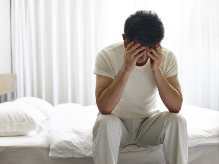 asian man painful and miserable sitting on bed head down covering face with hands. 스톡 콘텐츠