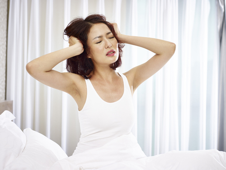young asian woman suffering from sleep disorder scratching head in bed. Stock Photo