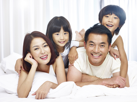 happy asian family with two children having fun in bed at home.