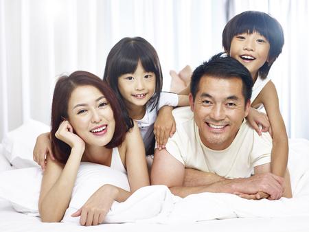 행복 한 아시아 가족 집에서 침대에서 재미 두 아이 함께.