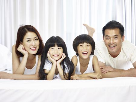 카메라 웃는 일 찾고 침대 앞에 누워 두 아이 함께 행복 한 아시아 가족.