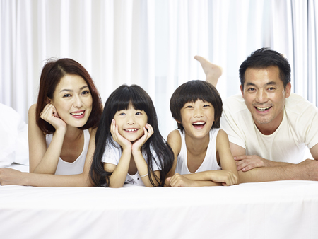 happy asian family with two children lying on front in bed looking at camera smiling. Stock fotó - 92608810