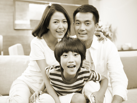 black and white portrait of a happy asian family looking at camera smiling