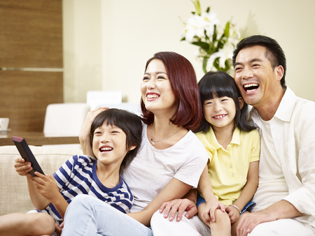 happy asian family with two children sitting on couch at home watching TV.