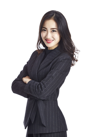 studio portrait of a young beautiful asian business woman, arms crossed, looking at camera smiling, isolated on white background.