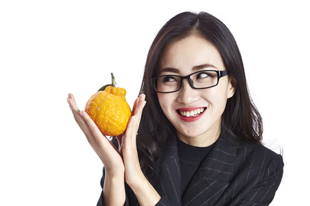 studio shot of a young asian business woman holding an ugli fruit, making a face, happy and smiling, isolated on white background.