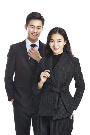 studio portrait of two young asian corporate executive, businessman and businesswoman, looking at camera smiling, isolated on white background. Imagens