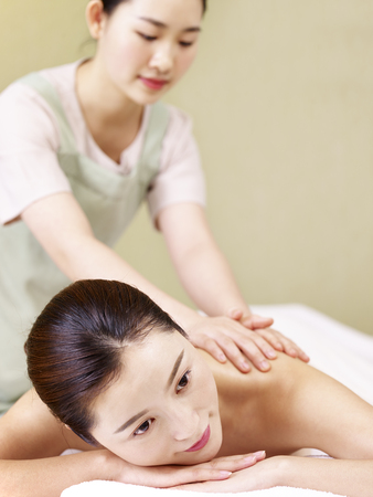 close-up of face of a beautiful young asian woman lying on front on bed receiving massage in spa salon. Stock Photo