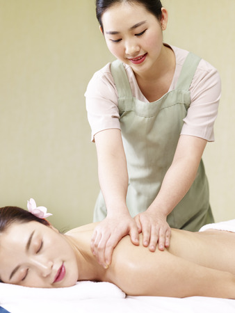 young asian masseur performing massage on woman in spa salon. Stock Photo