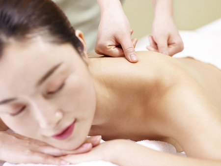 young asian woman lying in front on bed receiving massage in spa salon. Stock Photo
