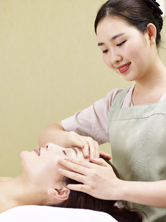 young asian masseur performing face massage on woman in spa salon