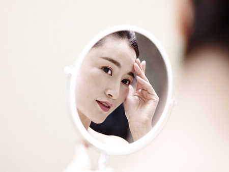 beautiful young asian woman looking at self in mirror, hand on forehead. Stock Photo