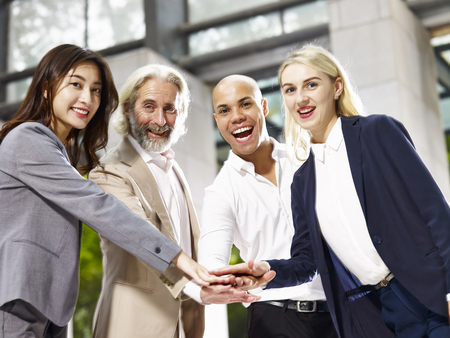 caucasian, asian and latino corporate business people putting hands together showing unity and team spirit Stock Photo