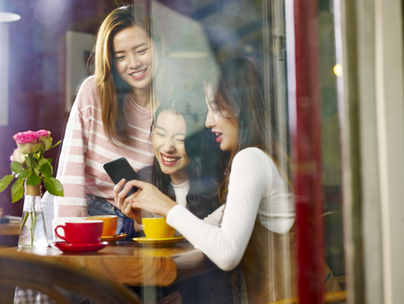 three beautiful young asian women playing with cellphone in coffee shop or tea house, shot through window glass.