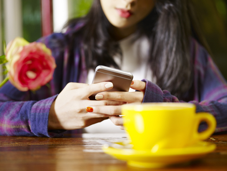 asian woman playing with mobile phone while drinking coffee, focus on hands. Stock Photo