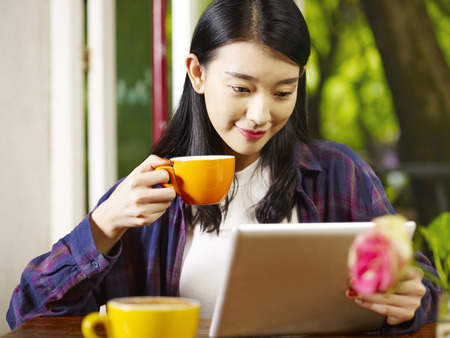 beautiful young asian woman using digital tablet while drinking cappuccino in coffee shop. Stock Photo