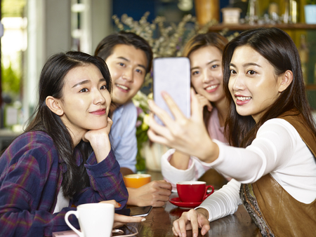 group of young asian adults man and women at coffee shop taking a selfie. 스톡 콘텐츠