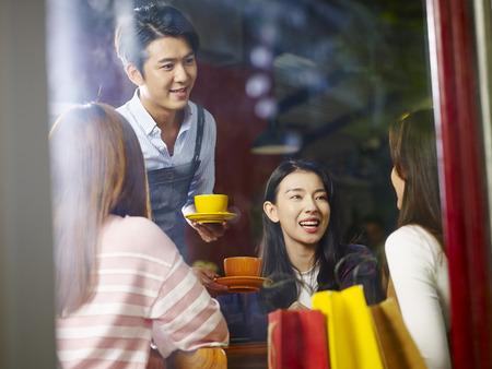 młody azjatycki kelner obsługujący klientów płci żeńskiej w kawiarni, zastrzelony przez szybę.