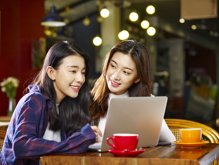two happy young asian women sitting in coffee shop looking at laptop computer together. 스톡 콘텐츠