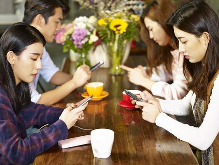 Cuatro jóvenes adultos asiáticos hombre y mujeres sentados en la cafetería jugando con el teléfono móvil con expresión facial muy grave.