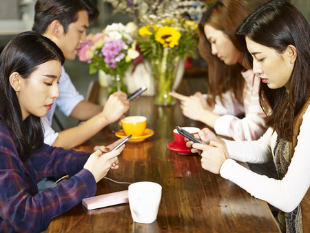 four young asian adults man and women sitting in coffee shop playing with mobile phone with very serious facial expression.