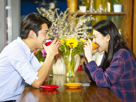 young loving asian couple sitting face to face drinking coffee.