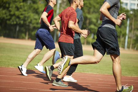 four asian young adults training running on track.