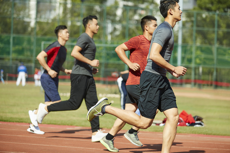 young asian adult athletes running training on track, side view.