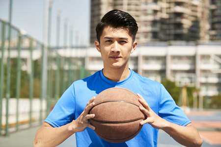 young asian male player holding a basketball looking at camera.