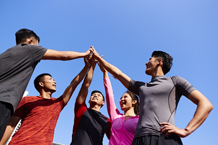 team of asian young adult sportsmen and sportswoman putting hands together to show unity and teamwork spirit. Stock fotó