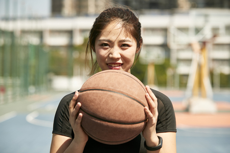 young asian woman holding a basketball looking at camera smiling. 免版税图像