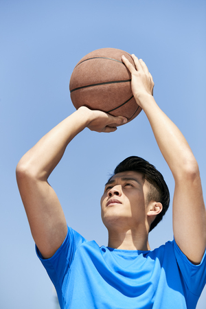 young asian male basketball player making a jump shot against blue sky background.