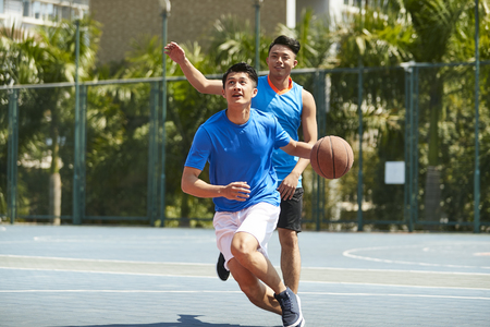young asian male basketball player playing one-on-one on outdoor court. Stock Photo