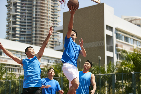 young asian adult male player playing basketball on a urban outdoor court.