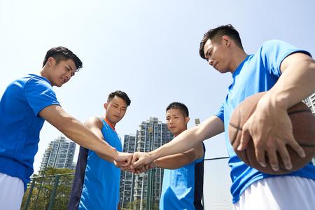 jonge Aziatische basketbalspelers die vuisten in elkaar zetten om eenheid te tonen voordat ze een spel spelen. Stockfoto
