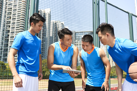 young asian basketball players discussing tactics using digital tablet at court side.
