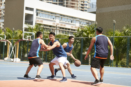 young asian adult players playing basketball on outdoor court. Фото со стока - 105788277