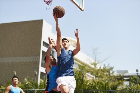 Joven jugador de baloncesto asiático subiendo por una bandeja mientras el oponente juega a la defensiva.